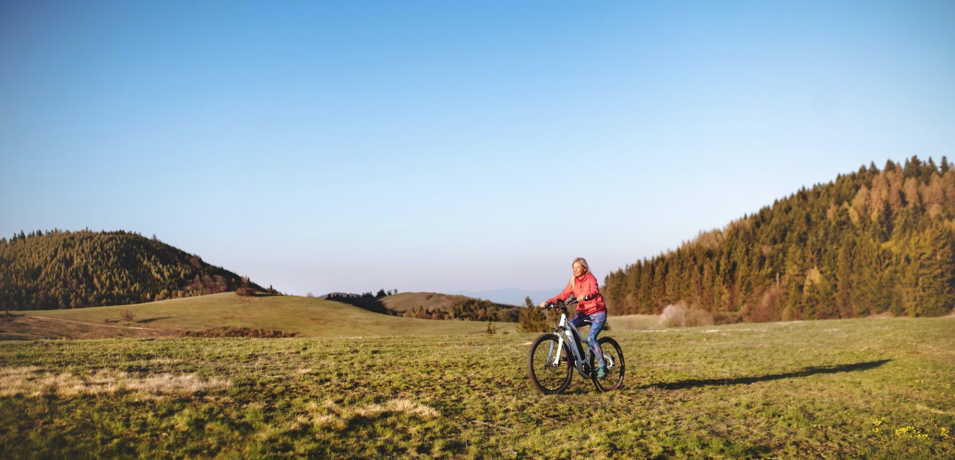 Active senior woman with e-bike cycling outdoors in nature